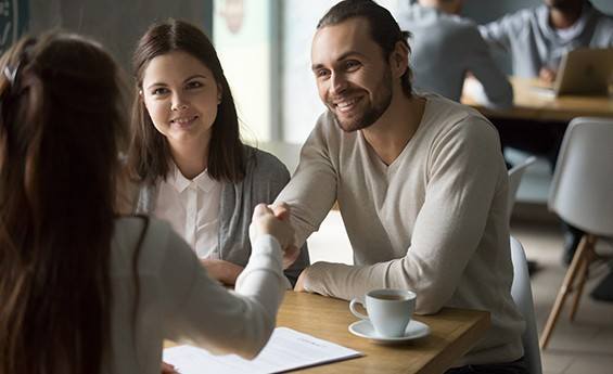 couple shaking hands with woman over coffee