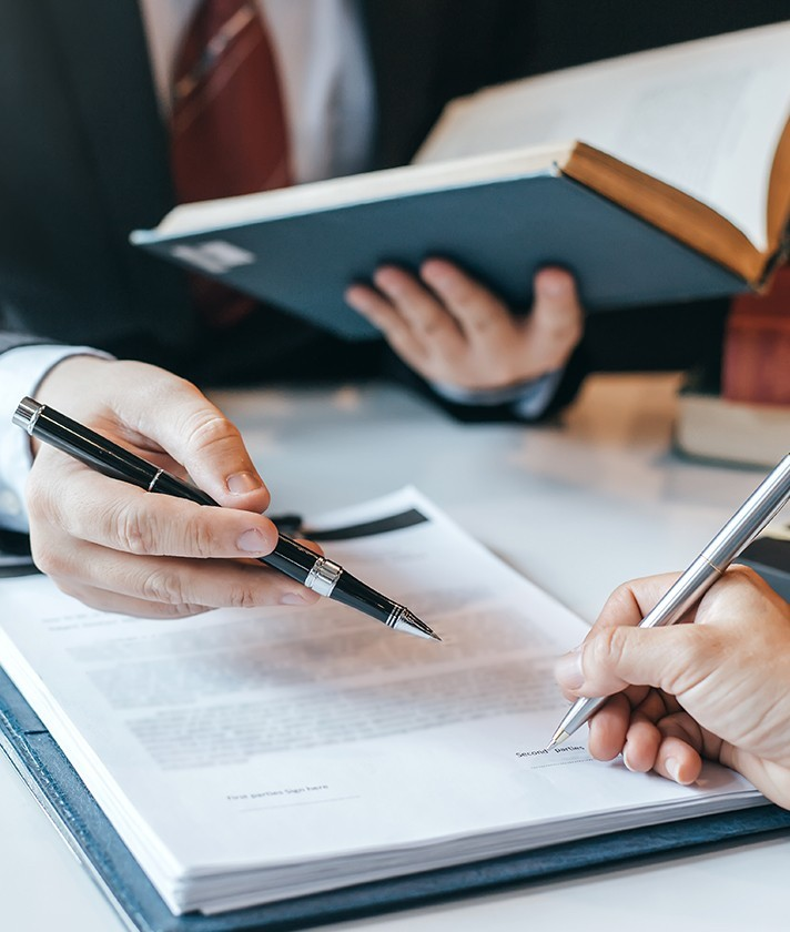 a man points out information on a document with a pen to a person signing the document