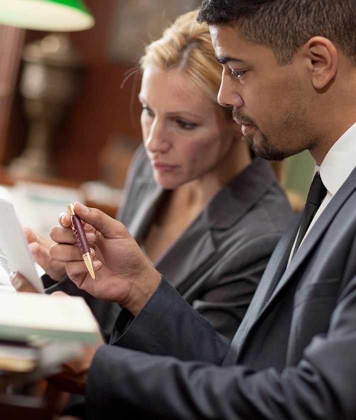 male and female businessperson look at a document